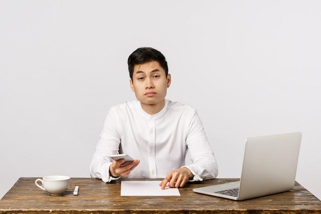 退屈したビジネスマン、仕事に疲れたオフィスワーカー、スマートフォンでスクロールフィード、疲れて目を細めて座っている机、眠そうな顔、疲れた退屈な準備レポート