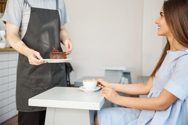 コーヒービジネスコンセプト - コーヒーショップで青いドレスで白人の美しい女性と話し、チョコレートケーキを与えるウェイターやバーテンダー。