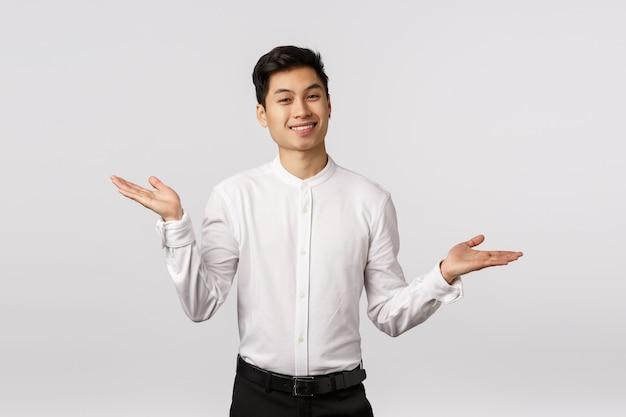 Беззаботный и беззаботный счастливый успешный молодой служащий в белой рубашке, брюках, разводит руками в стороны и пожимает плечами с расслабленным, облегченным выражением лица, улыбается, не знает и не заботится