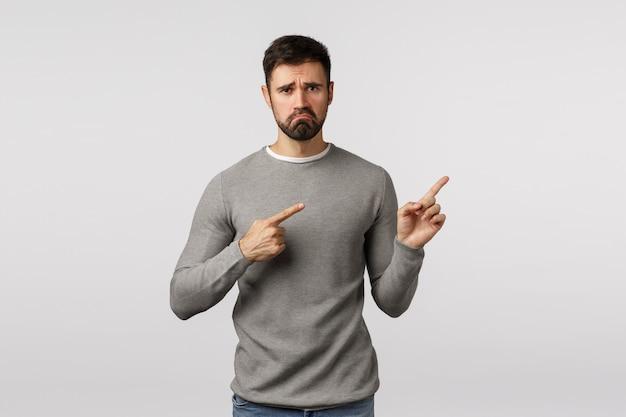 灰色のセーターを着た悲観的な落ち込んで孤独な悲惨なハンサムなひげを生やした男、右上隅を指して、不機嫌そうな顔を引っ張って、顔をしかめ、文句を言う、,や後悔を感じ、悪いニュースを表示する