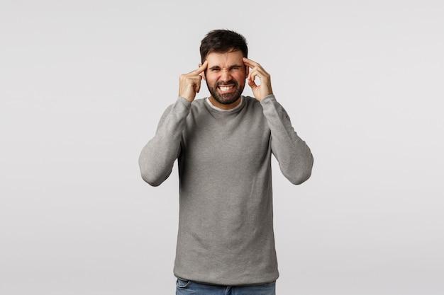 Концепция похмелья, праздников и здравоохранения. раздраженный и взволнованный взрослый бородатый мужчина, морщась от боли, стискивает зубы, трогает виски, массажирует голову, ощущая сильную головную боль, страдает мигренью