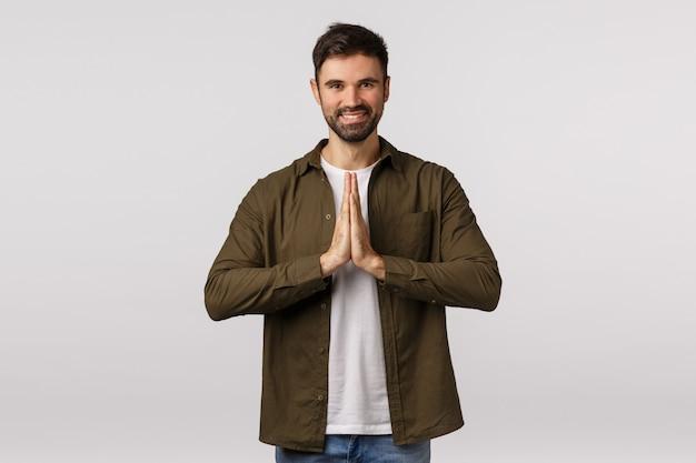 陽気でリラックスしたフレンドリーな笑顔の白人男性が一緒に祈り、ニヤリと、瞑想、またはヨガの練習を終えて手のひらを押し、感謝の気持ちを表現するためにお辞儀をする