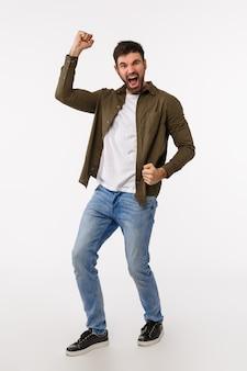 達成、成功、賞のコンセプト。カジュアルな服装のひげを持つ男性を喜ばせて喜ばせ、良いニュース、拳ポンプとダンスを祝い、明るい笑顔