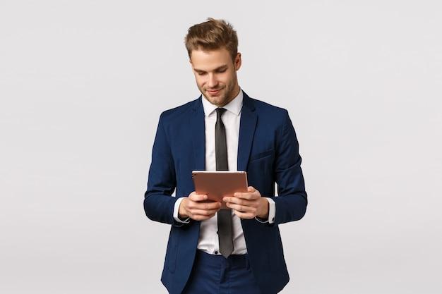 企業、ビジネス、金融の概念。ハンサムな自信とエレガントな若いひげを生やした金髪の男、男性起業家立っているオフィス、作業、デジタルタブレットを保持