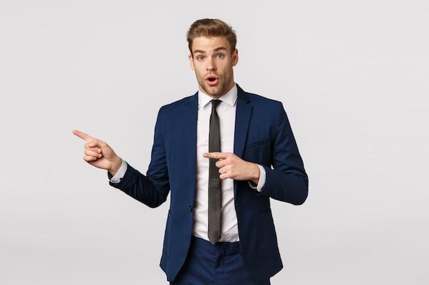 Вау, чувак, ты видел это? удивленный красивый бизнесмен, задающий вопрос о странной странной вещи, указывающий на левые указательные пальцы и выглядящий озадаченным,