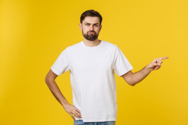 イライラし、前方を向く孤立した黄色の壁の上のハンサムな男。