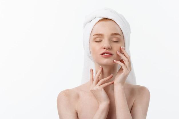 白の彼女の顔に化粧品クリーム治療を適用する美しいモデル。