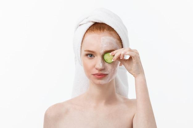 美しいきれいな肌を持つ魅力的な若い女性。白いマスクとキュウリ。美容トリートメントと美容スパセラピー。