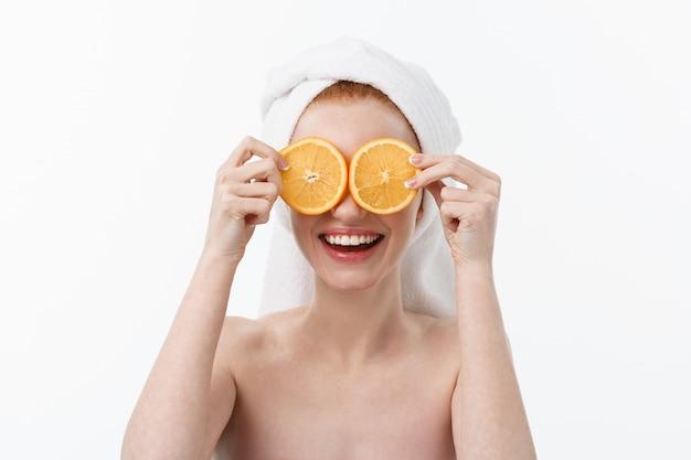 Отличная еда для здорового образа жизни. красивая молодая без рубашки женщина, держащая кусок оранжевого восстания против.
