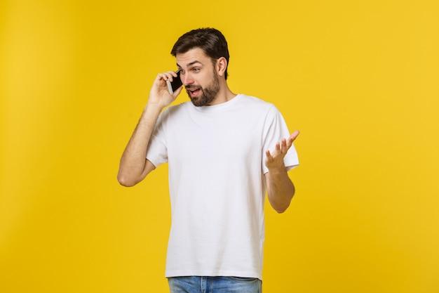 Изолированный портрет серьезного человека говоря на телефоне.