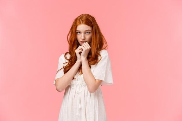 恥ずかしがり屋のカワイイ、白いドレスを着た赤毛のヨーロッパの女の子、恥ずかしがり屋でかわいい、赤面、額の下から見て優柔不断で恥ずかしがり屋、ピンクの壁の上に控えめに立って