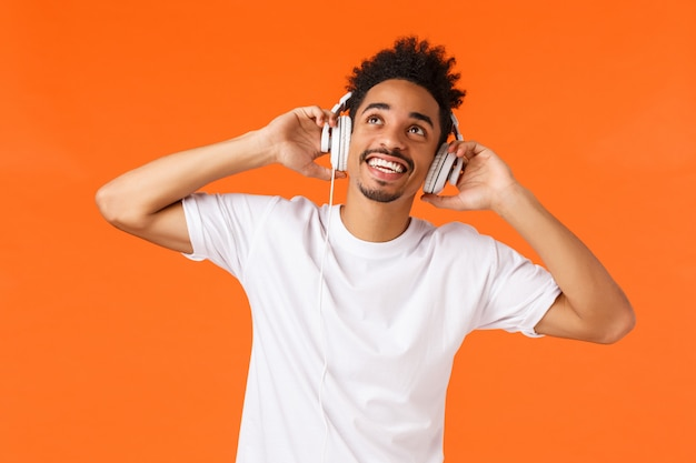 Восторженный беззаботный, улыбающийся афроамериканец, наслаждающийся прослушиванием музыки, держась за руки в наушниках, улыбается и смотрит вверх, чувствуя удовольствие от удивительных ударов наушников, оранжевая стена