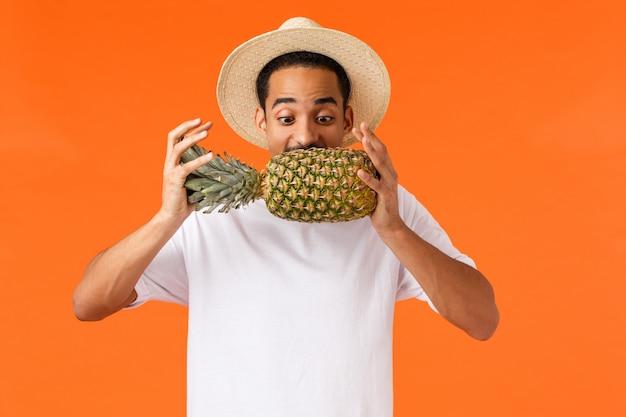 Забавный красивый хипстерский парень, афроамериканский турист, наслаждающийся отпуском, пробующий укус ананаса, смотрящий на фрукты, радостно стоящий на оранжевой стене, словно путешествует по жарким странам зимой