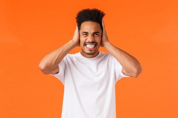 不快感と頭痛を感じる不満のアフリカ系アメリカ人の男、歯を食いしばって、不快な大きな音を聞いて耳をふさいで、隣人に悩まされ、オレンジ色の壁
