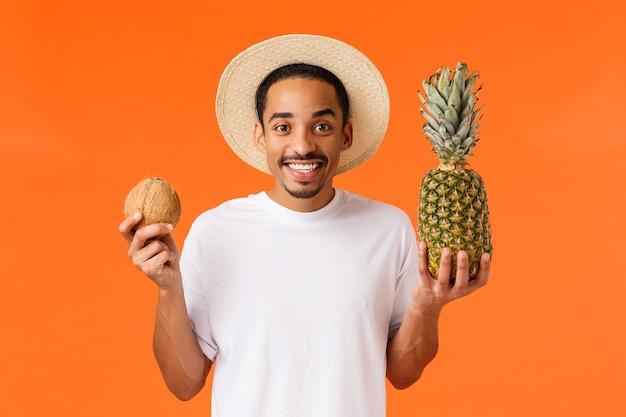 Концепция путешествий, отдыха и досуга. возбужденный счастливый молодой афроамериканский парень забронировал отель и поехал за границу, наслаждаясь солнцем и вкусными фруктами, держа кокос и ананас