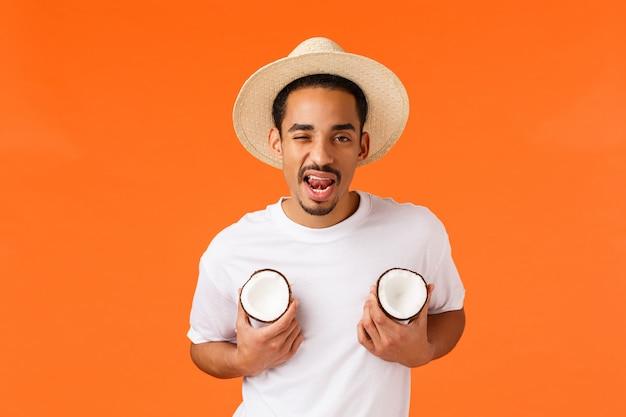 Нахальный и кокетливый афроамериканский хипстерский парень, ведущий себя как мачо, показывающий язык, держащий кокосовые орехи, любит грудь и соблазняющий, стоящая оранжевая стена