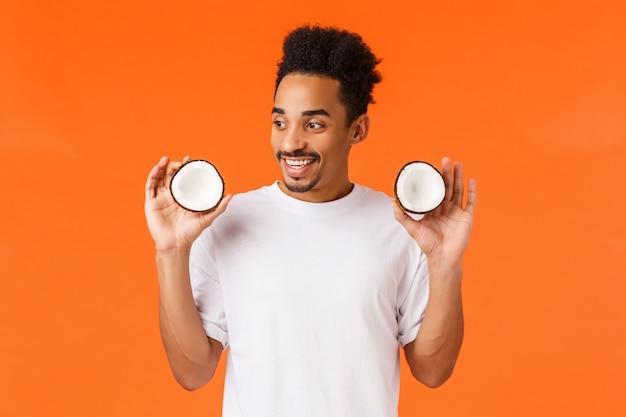 Жизнерадостный афроамериканец в отпуске пробует тропические фрукты, держит в руках две части кокоса и улыбается изумленно, ест и наслаждается летним курортом, стоит в восторге от оранжевой стены