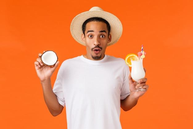 Роскошный курорт, концепция туризма и отдыха. портрет талии вверх афро-американский красивый возбужденный мужчина держит кокос и освежающий коктейль, улыбается позабавило, весело, наслаждаясь роскошный курорт