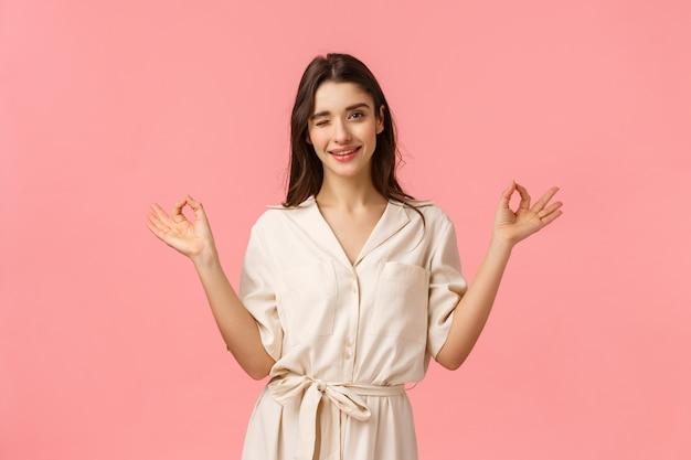 Сохраняйте спокойствие и отправляйтесь за покупками. веселая дерзкая и женственная молодая брюнетка в красивом платье, показывает жест дзен, медитирует и подмигивает кокетливо стоящая розовая стена