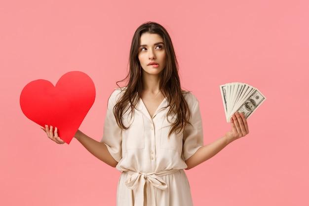ロマンス、富、現代のライフスタイルコンセプト。ドレスを着た魅力的な見栄えのブルネットの女性、現金、お金、愛の心を保持し、唇を噛んで右上隅がわからない、決定を下す