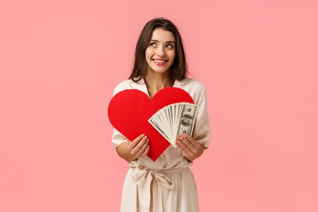 愛、優しさと関係の概念。裕福な金持ちと真の愛を夢見て、お金のドルと心のカードを保持している、笑顔の画像のもの、ピンクの壁を見てかわいいと愚かな女の子