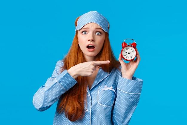 ショックを受け、心配している、心配しているかわいい赤毛の女の子がイライラし、神経質な表情で目覚まし時計を指して、遅れている、正しい時間を設定する方法がわからない、ナイトウェアの青い壁に立っている