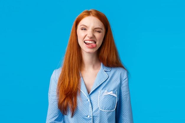 Беззаботная и забавная милая рыжая девочка-подросток не хочет спать во время ночевки с подружками, показывает язык и дурачится, высмеивает гримасы, радостно подмигивает, носит пижаму, голубые стены