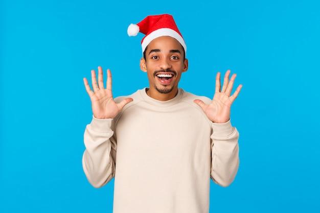 サンタ帽子でプレゼントを引く男。陽気なアフリカ系アメリカ人の若い男は何かをつかむ、手を上げてキャッチを待って、嬉しそうに笑って、冬の休日、青い壁を祝う