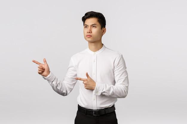 側を指している白いシャツと陽気な笑顔のアジアの若い起業家