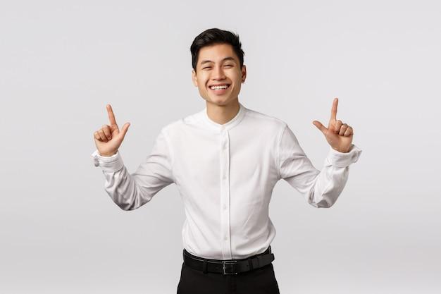 Жизнерадостный усмехаясь азиатский молодой предприниматель с белой рубашкой указывая вверх