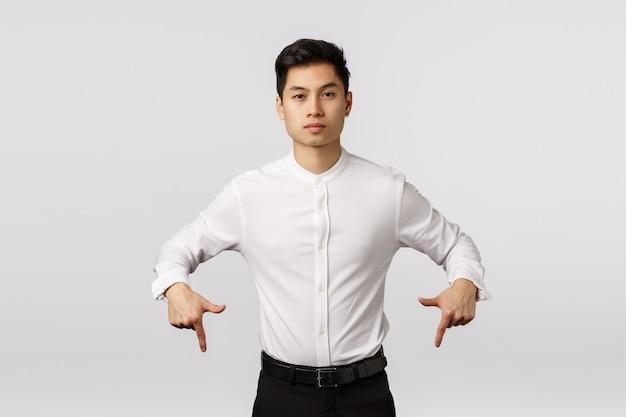 Жизнерадостный усмехаясь азиатский молодой предприниматель с белой рубашкой указывая вниз