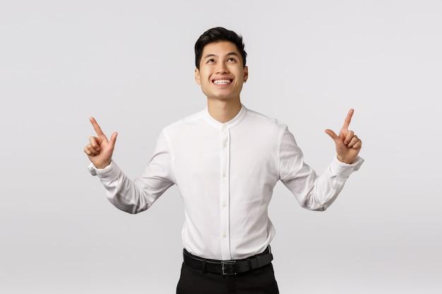 上向きの白いシャツと陽気な笑顔のアジアの若い起業家