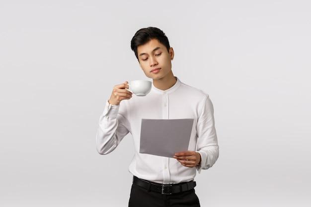 Жизнерадостный усмехаясь азиатский молодой предприниматель при белая рубашка держа документы и выпивая кофе