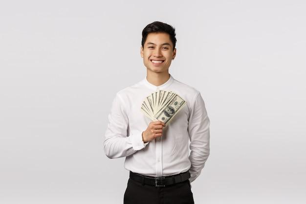 紙幣を保持している白いシャツと陽気な笑顔のアジアの若い起業家