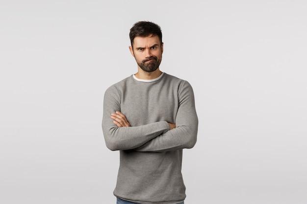 組んだ腕を持つ灰色のセーターのひげを生やした男