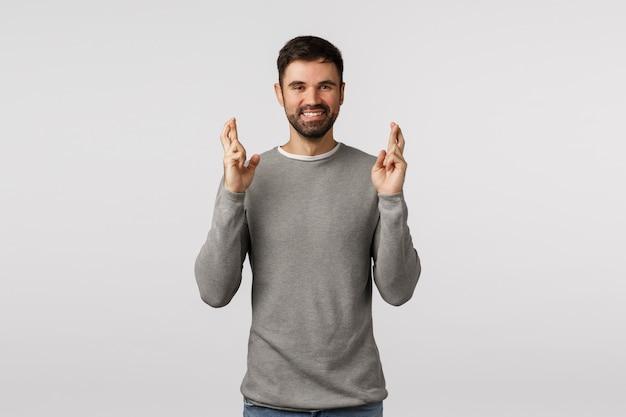 幸運を祈る灰色のセーターのひげを生やした男