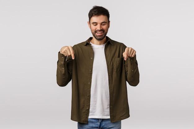 Бородатый парень в коричневом пальто, указывая вниз
