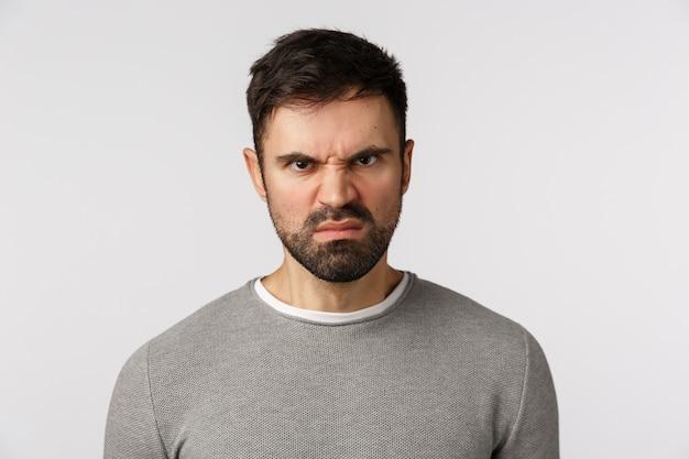 怒った顔で灰色のセーターのひげを生やした男