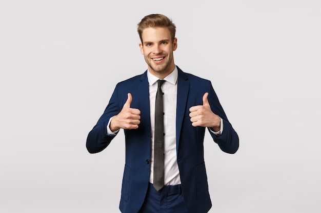 Привлекательный белокурый бородатый бизнесмен показывает палец вверх