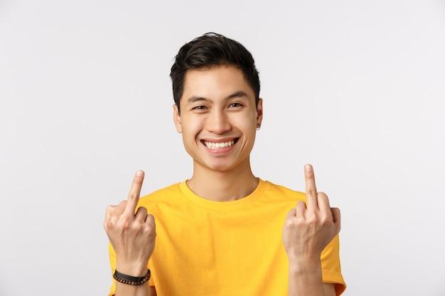 Милый азиатский человек в желтой футболке показывая средние пальцы