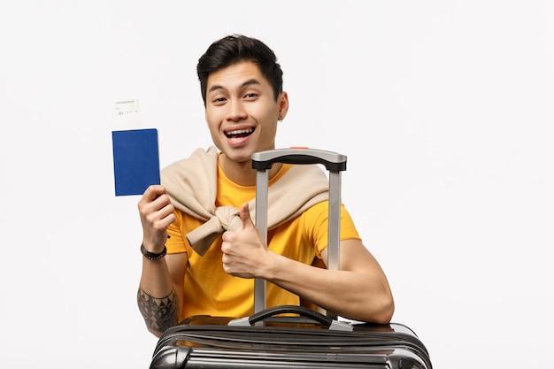 Милый азиатский человек в желтой футболке готов к путешествию с паспортом