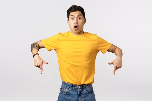 Милый азиатский человек в желтой футболке указывая вниз