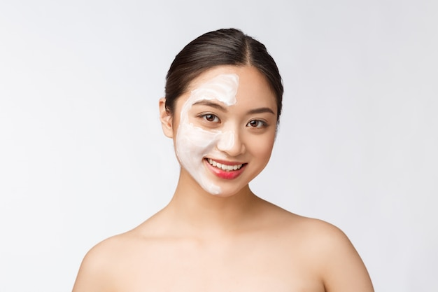 Очаровательная приятная женщина наносит крем на половину лица
