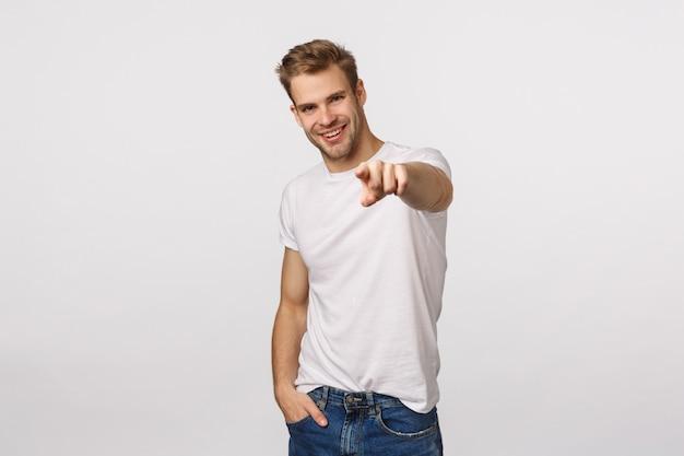 Красивый белокурый парень с голубыми глазами и белой футболкой указывая