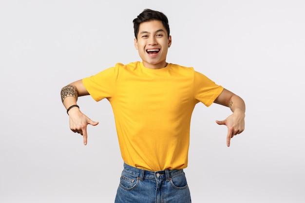 Красивый молодой азиатский человек в желтой футболке указывая вниз