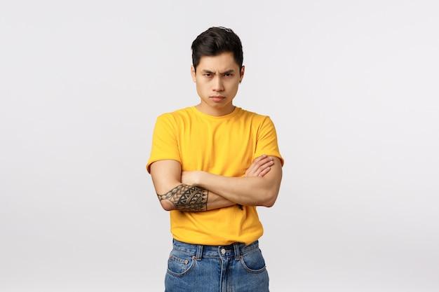 Красивый молодой азиатский человек в желтой футболке со скрещенными руками