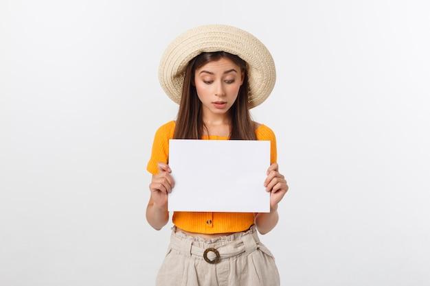Красивая женщина в шляпе держит чистый лист бумаги