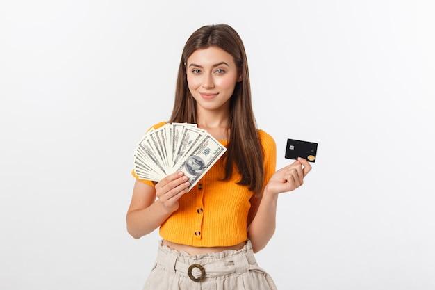 Красивая женщина с оранжевой блузке держит кредитную карту и деньги