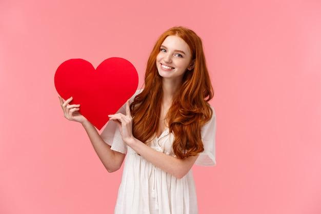 お祝い、愛と関係の概念。バレンタインの日に同情を告白するかわいい十代の少女、一緒に行くプロムを求めて、白いドレスに赤い髪のガールフレンド、大きな赤いハートを見せて、笑顔