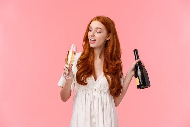 パーティー、二日酔い、お祝いのコンセプト。幸せで陽気な、屈託のない見栄えの良い赤毛の女性がグラスからシャンパンを飲んで、ボトルを持って、酔って、ピンクの上に立って無駄に